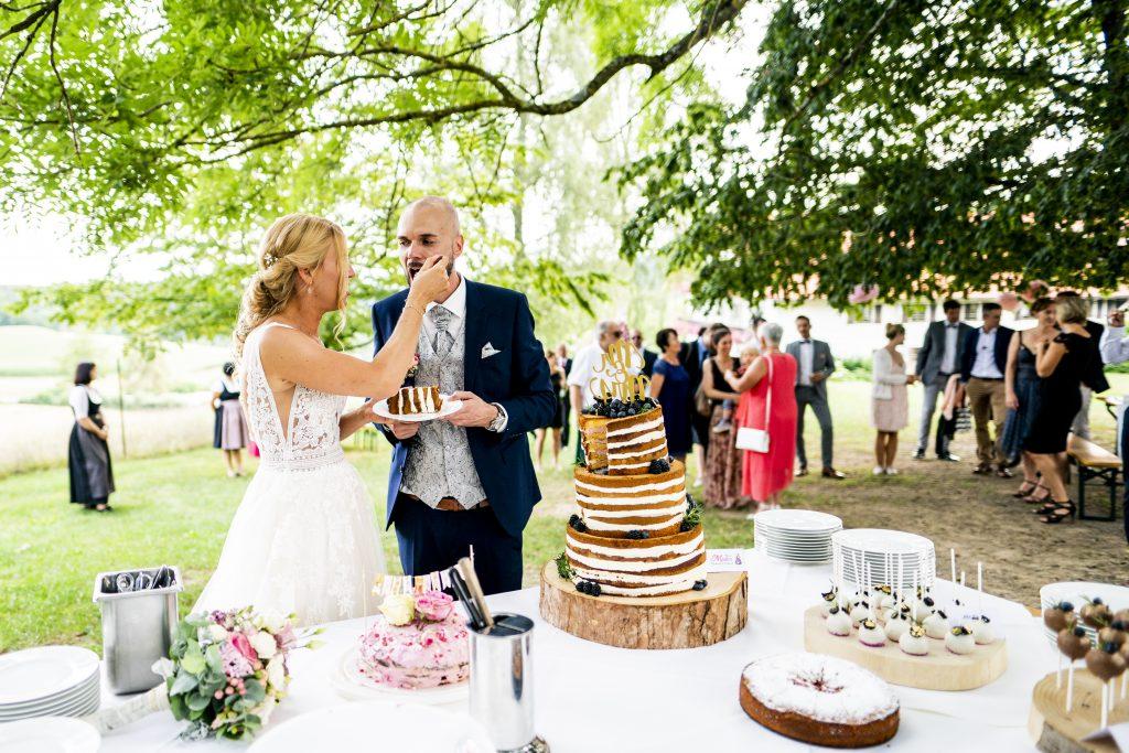 Der Anschnitt der Hochzeitstorte im Freien in Wild-Berghof Buchet in Bernried | KK-Fotografie