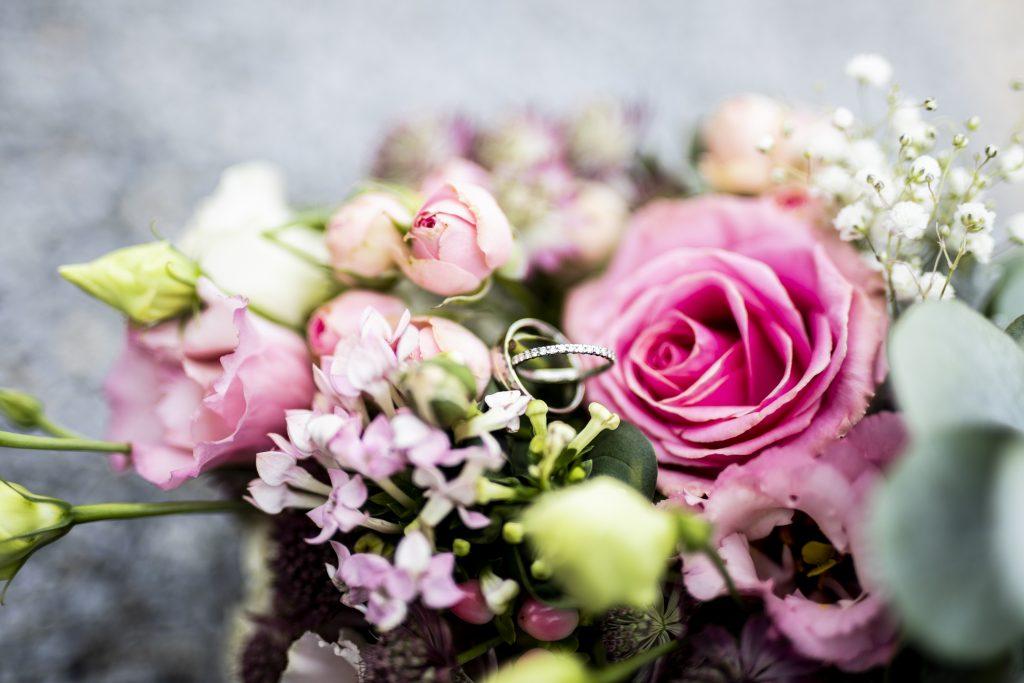 Ein Bild eines Eheringes und Hochzeitsstrauß in Bernried | KK-Fotografie